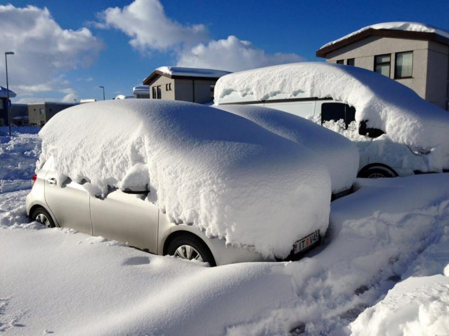 Heavy snowfall barying cars in a parking lot in Iceland