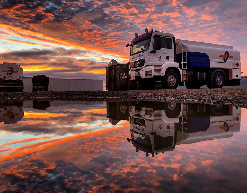 Oil truck parked along the ocean with a beuatiful sunset in the background